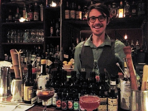 Burton poses behind a selection of bitters. The Blood & Sand cocktail is on the left, the Jack Rose is the pink drink near center.
